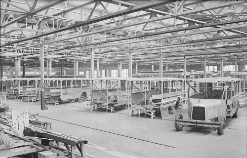 A large factory with a row of buses in different states of completion. One has a bus body on wheels, but others are just metal shells waiting for wheels and interior fixtures..
