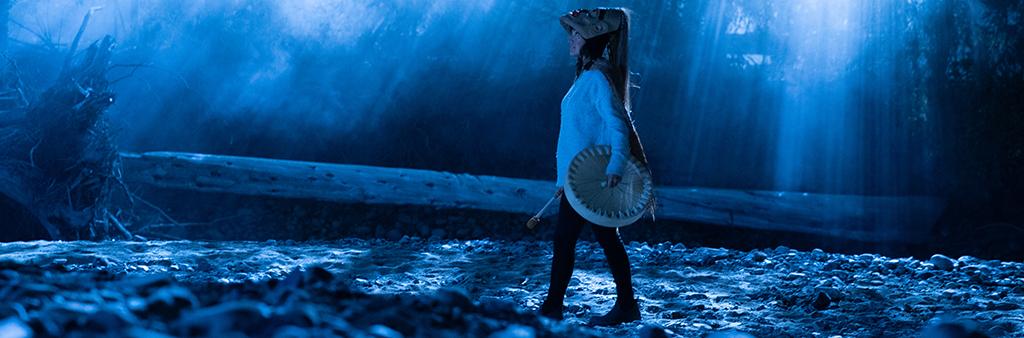 Image depicts female dancer holding drum.