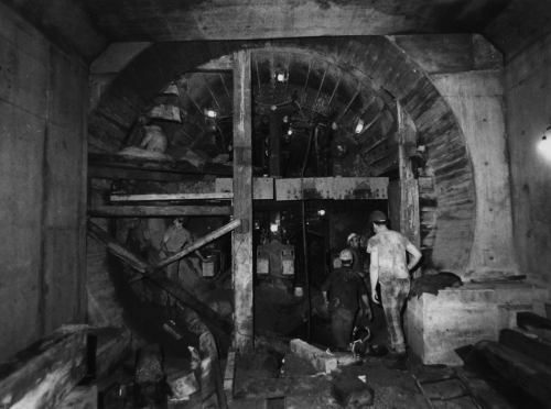 Workers standing in newly constructed subway tunnel.