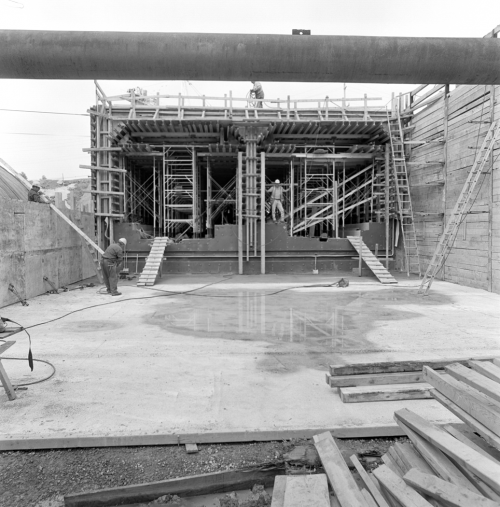 Foreground shows hoarding and concrete floor. Background shows two box tunnel structures with scaffolding.