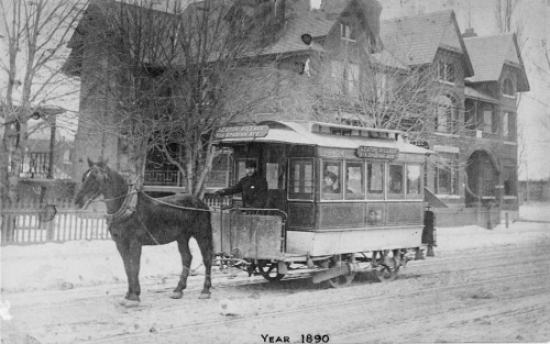 A small streetcar pulled by one horse. The driver is outside on a platform at the front of the car.