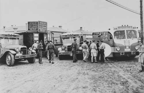 Uniformed men boarding buses.