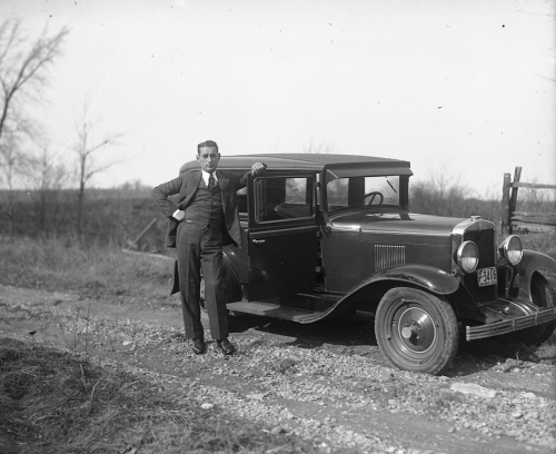 A man is standing in front of an automobile on a dirt road. His hand is resting on the open door.