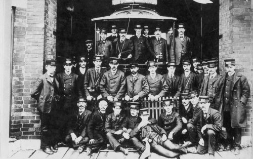 A group of men in uniforms poses in front of a streetcar at the door of a garage.