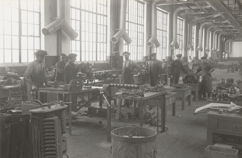 A large room with enormous windows. Workers are repairing machinery at tables.