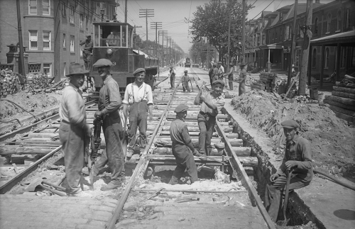 Men are digging up the brick road around streetcar tracks. They are smiling at the camera.