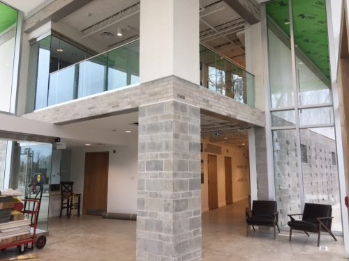 In the middle of the photo is an interior pillar that spans two floors; the two story pillar supports a corner of the second floor lobby. Bottom of the photo shows main floor lobby including polished concrete floors, windows, two closed doors to the storage room and kitchen and two lobby chairs on the right hand side; to the left of the interior pillar are some construction materials on a trolley, a small chair and the closed door to the office. At the top of the photo is the glass barrier that sections off the second floor lobby; ceiling elements including a light, vents are in view.