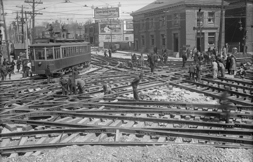 Many men digging the road up around a network of streetcar tracks going in every direction.