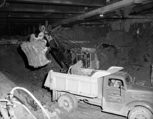 In an underground space, the bucket of an excavating machine moves dug-up earth into the back of a dump truck.