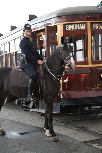 Policeman on dark brown horse in front of red streetcar with yellow trim.