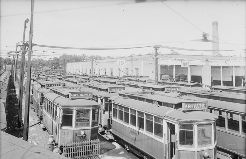 Several rows of streetcars in front of a large brick garage.