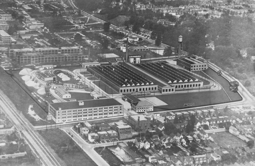 An industrial complex, including two long, low buildings with clerestory windows, a four-storey office building, a streetcar track loop, and a water tower.