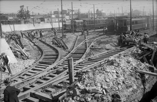 Workers installing four sets of streetcar tracks that all converge into one.