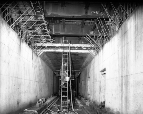 A worker in a square concrete tunnel carries a bucket up a ladder to a second level.