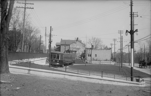 A streetcar drives around a large oval of tracks with a lawn in the centre and houses in the background.