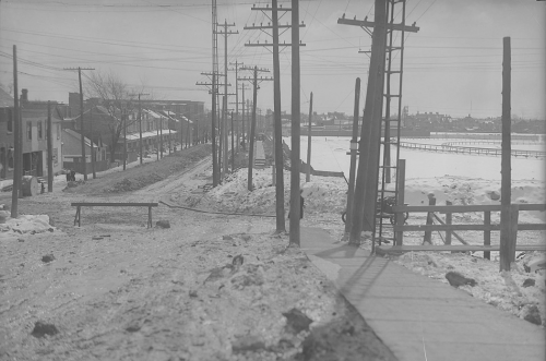 A large open space containing only a few fences. It is covered in snow. It is bordered by roads with houses on them. I