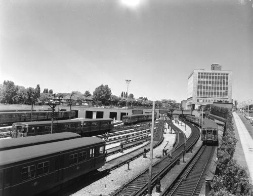 Several subway trains sit on tracks. In the distance is a square, modernist office building with many windows.