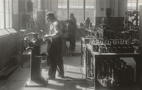 A worker is polishing equipment parts on a lathe. Behind him is a table filled with cylindrical metal parts.