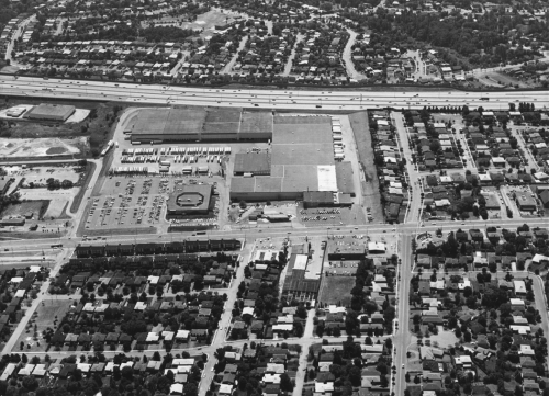 Foreground shows subdivision. Middle of the picture shows an industrial building. Background shows highway and subdivisions.