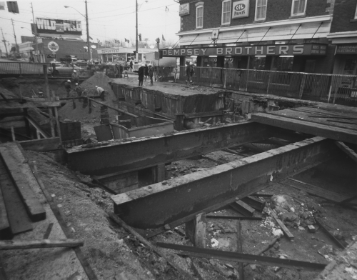 Beams over excavated area. Workers inside fenced area near hole. Dempsey Brothers store and gas station in background.