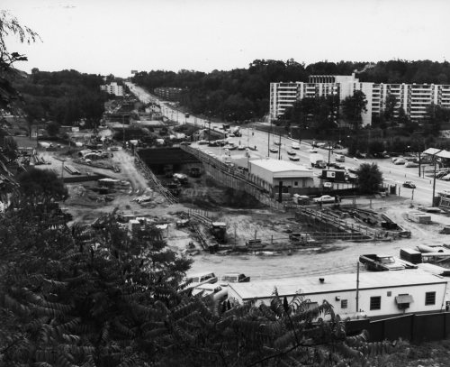 Site of excavation with workers' trailers. Far side of Yonge Street shows apartment buildings