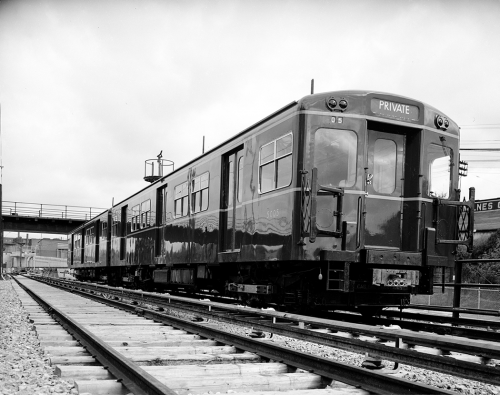 A shiny subway car sits on the tracks.
