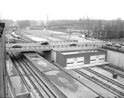 Subway tracks and a brick garage with four doors sit under a bridge.