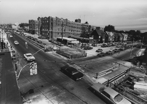 McAlphine sign at construction site. Traffic in streets. Background shows apartment building and houses along street.