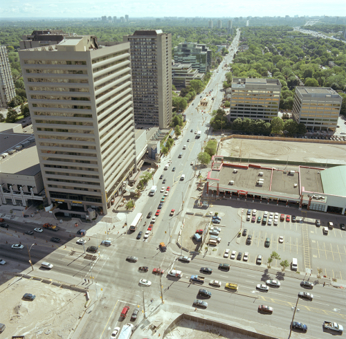 Traffic on roads, office towers, and shopping centre with parking lot. Background shows green space.