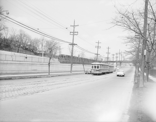 An older streetcar drives up a street, while a subway train can be seen on an embankment behind it.