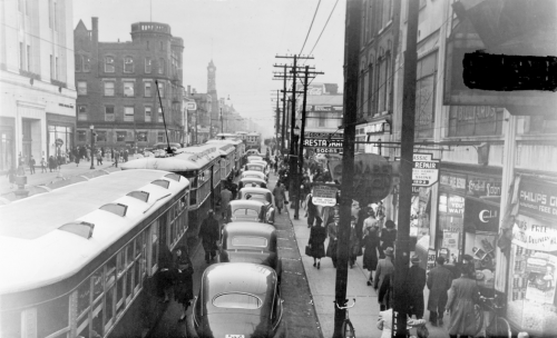 A bumper-to-bumper line of streetcars and motor cars on a city street.