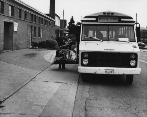 A man is sitting in a wheelchair on a ramp extending from the side of a bus.