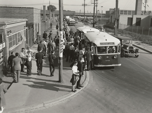 Crowds of people awaiting buses in an industrial area.
