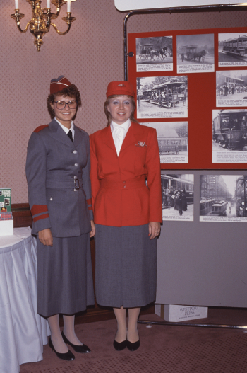 Two uniformed women standing near display. One woman is wearing a grey uniform with burgundy details. The other woman is wearing a grey skirt, white blouse and red blazer with a red cap.