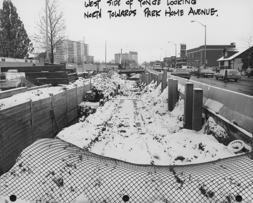 Snow covered excavated trench for subway tunnel with traffic on Yonge Street.