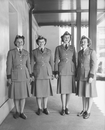 Four women in uniform with hats.