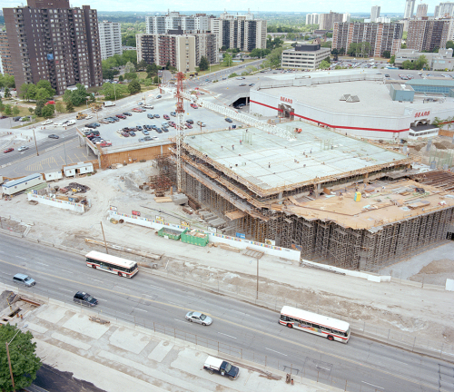 Foreground shows road with TTC buses and cars. Middle shows station construction near Sears wing of Fairview Mall. Background shows apartment buildings and office towers.