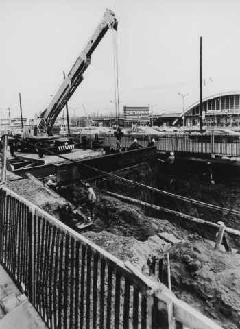 Crane and workers at excavated pit. Cars and mall in background.