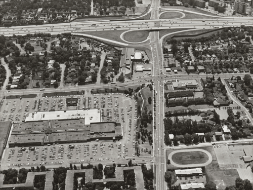 Foreground shows mall, parking lot, and subdivisions. Background shows highway and subdivisions.