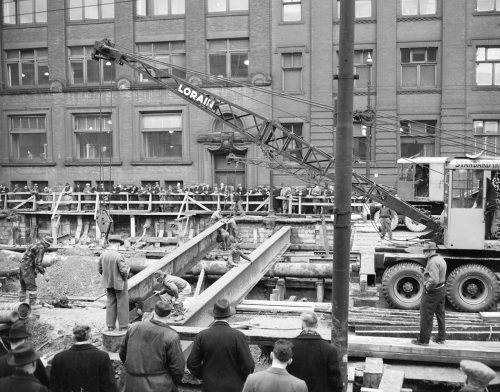 A crane lowers a large metal beam over an excavation, while workers guide the beam into place.