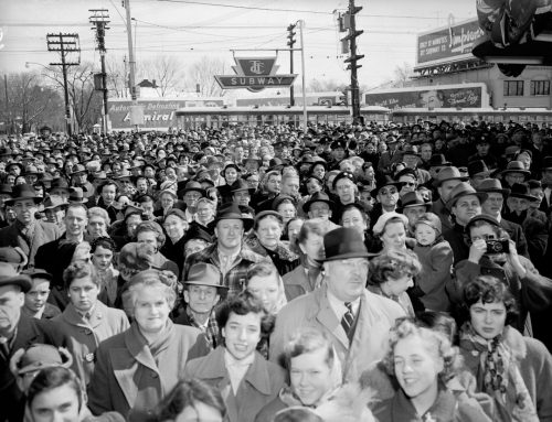 People in a large crowd smile at the camera. Behind them is a TTC subway sign.