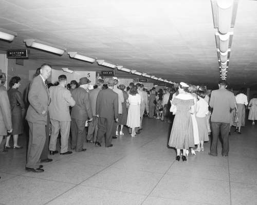 People are standing in lines in a long room with rows of lights on the ceiling.