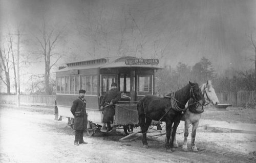 """A streetcar pulled by a black horse and a white horse. A man in a winter coat and hat is standing on the step of the streetcar. The sign on the front says """"High Park via Queen."""""""