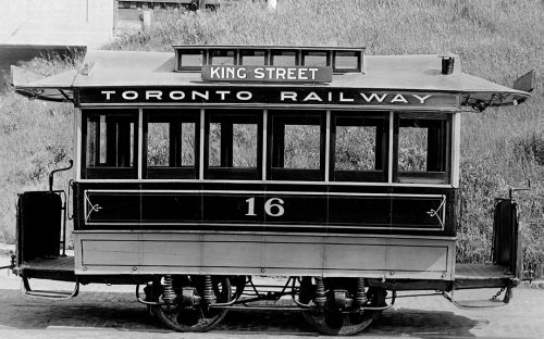 """A small streetcar with six windows on each side, and four wheels. It is painted black and white. The sign on the roof says """"King Street"""" and """"Toronto Railway."""""""