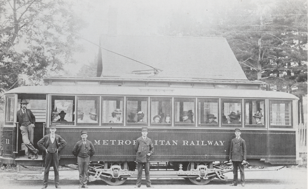 An electric streetcar with large windows. There are passengers inside looking out, and several men in drivers' uniforms are standing in front.