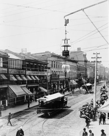 Streetcars drive down a street lined with brick buildings containing stores.