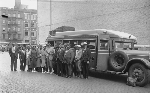 A group of Black people stands in front of a small bus. Behind them is a large brick wall probably the side of a theatre. In the background is a downtown street with stores.