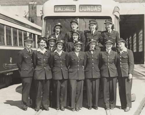 Thirteen uniformed women standing in front of streetcar in yard.