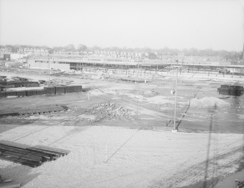 Foreground shows cleared area with rails for track installation. Background shows construction of large building.