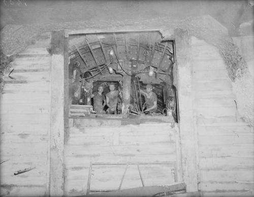 Three men looking through hole to larger excavated area.